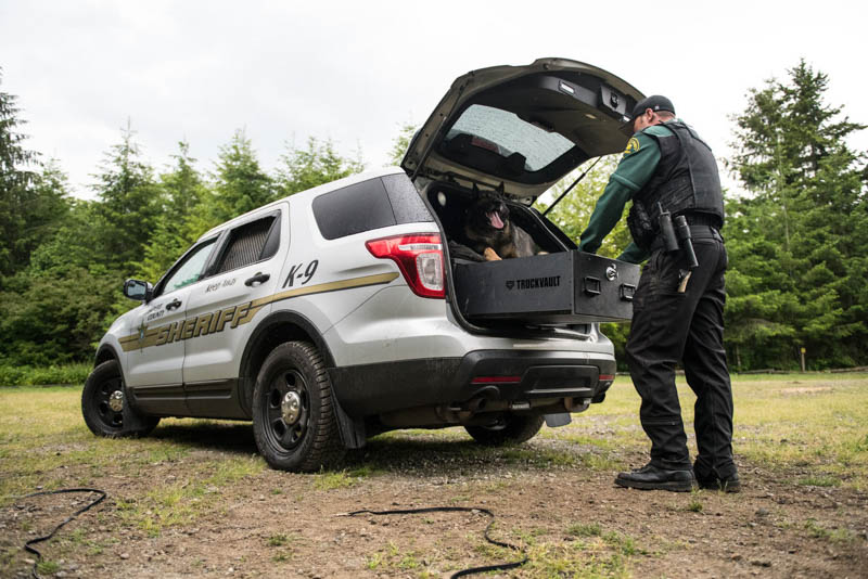 A silver, police department Ford Explorer with a dog and an officer opening a TruckVault.