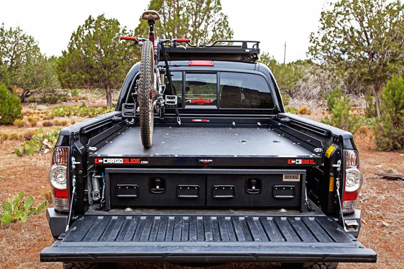 the rear of Toyota Tacoma with a TruckVault in the bed. There is also a mountain bike on top of the TruckVault.