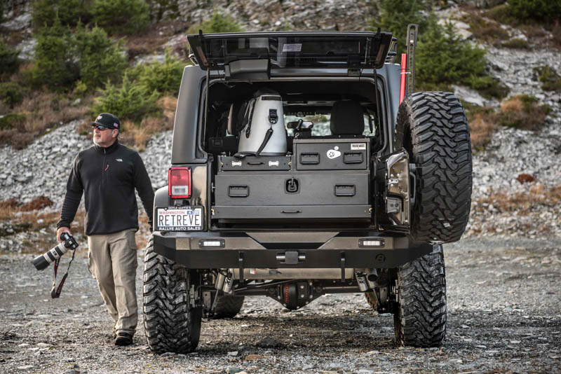 A silver Jeep Wrangler Unlimited with a custom TruckVault and a man carrying a camera.