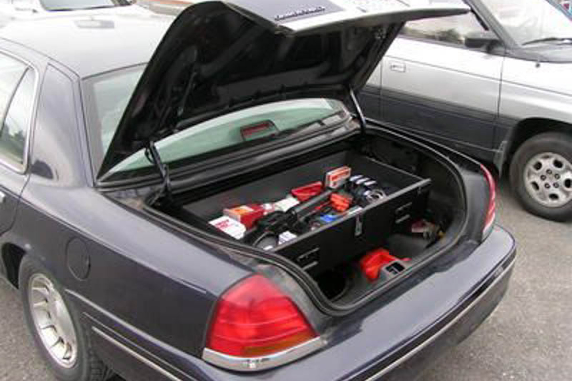 A navy Ford Crown Victoria police vehicle with a TruckVault in the trunk.