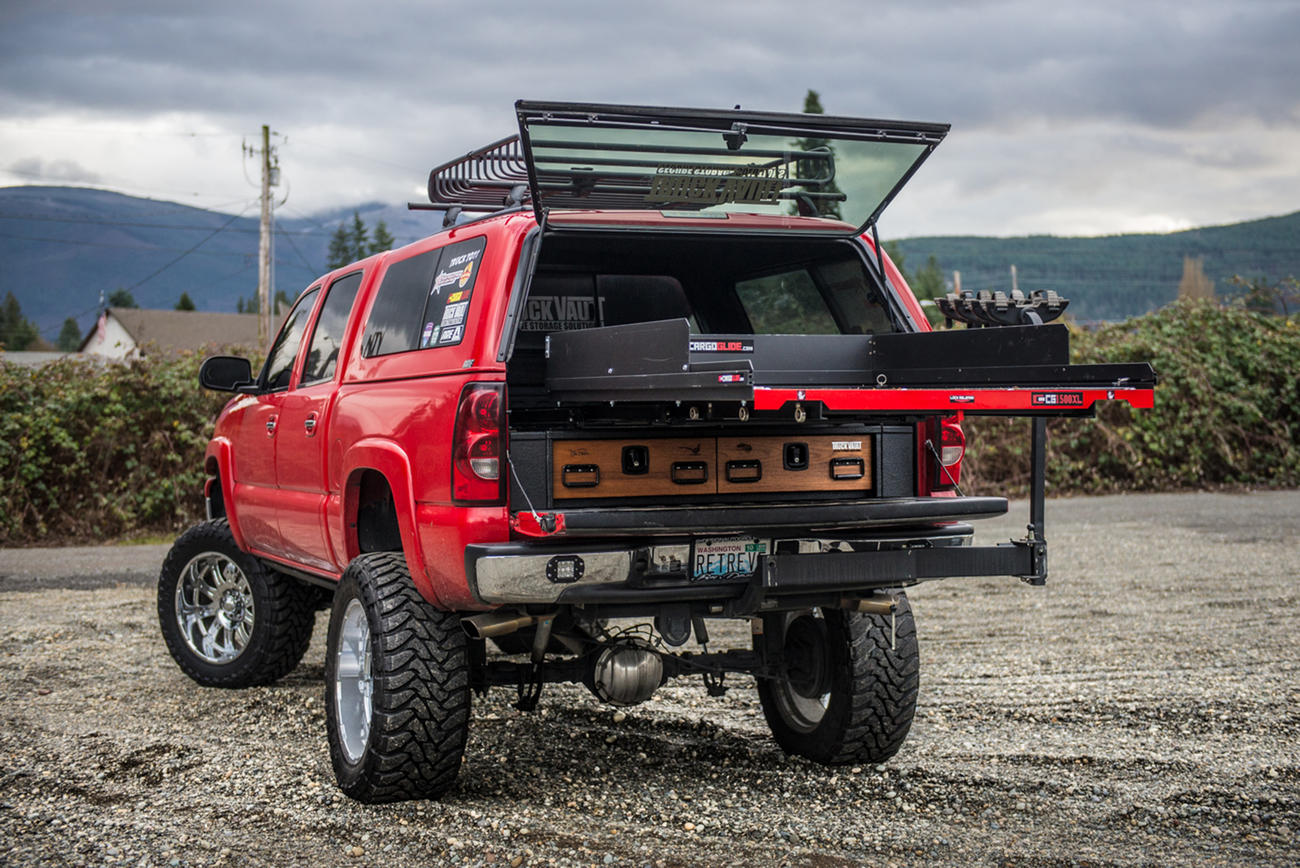 A red Chevy Silverado with a TruckVault and a CargoGlide on top of it.