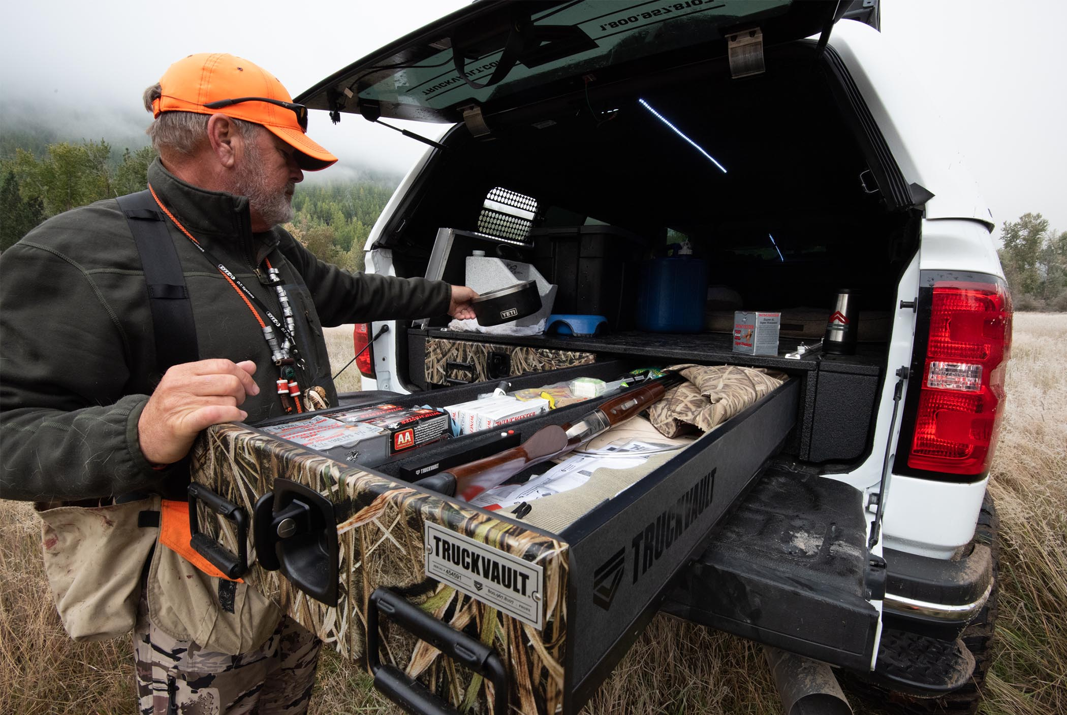 A pheasant hunter opening a TruckVault with a shotgun secured in the drawer.
