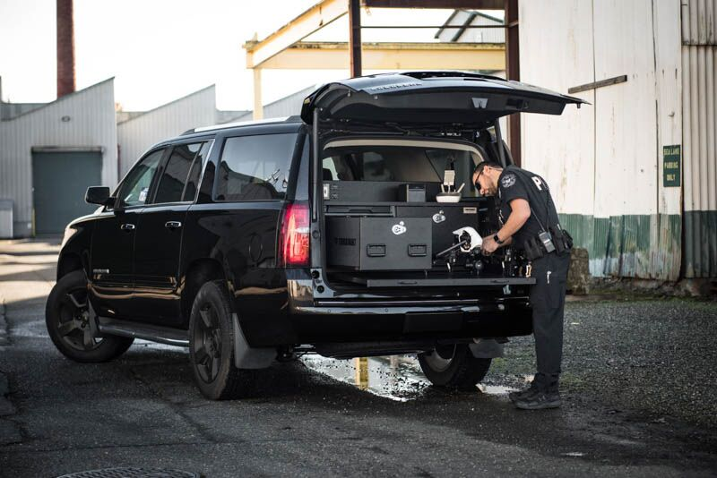 A black Chevy Tahoe with a police officer setting up his drone on his TruckVault pullout table.
