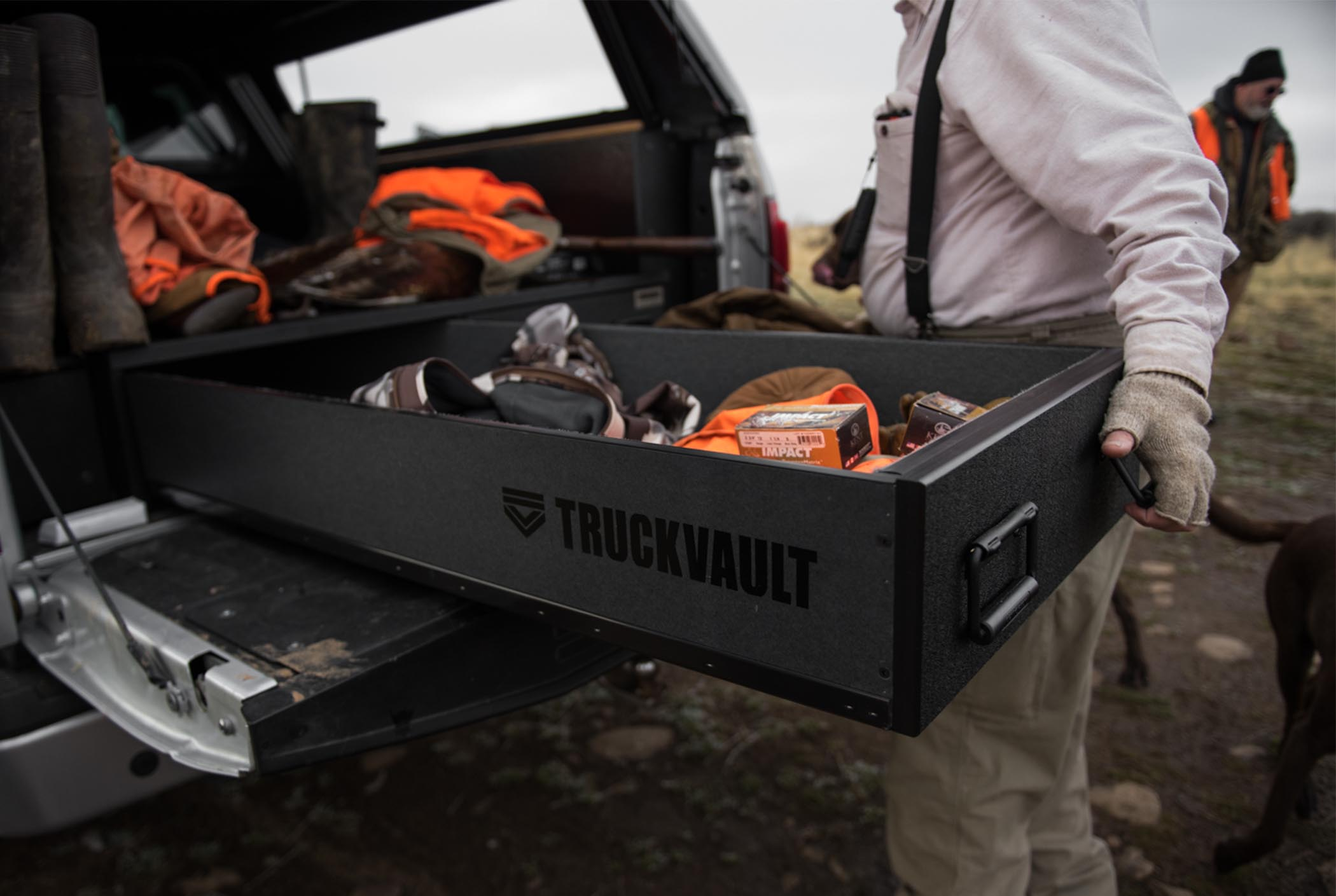 A man opening a covered bed TruckVault system that is securing upland bird hunting equipment.