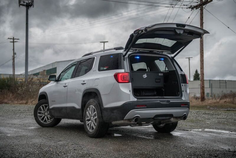 A silver GMC Acadia on a gravel road with a TruckVault in the cargo space for secure storage.