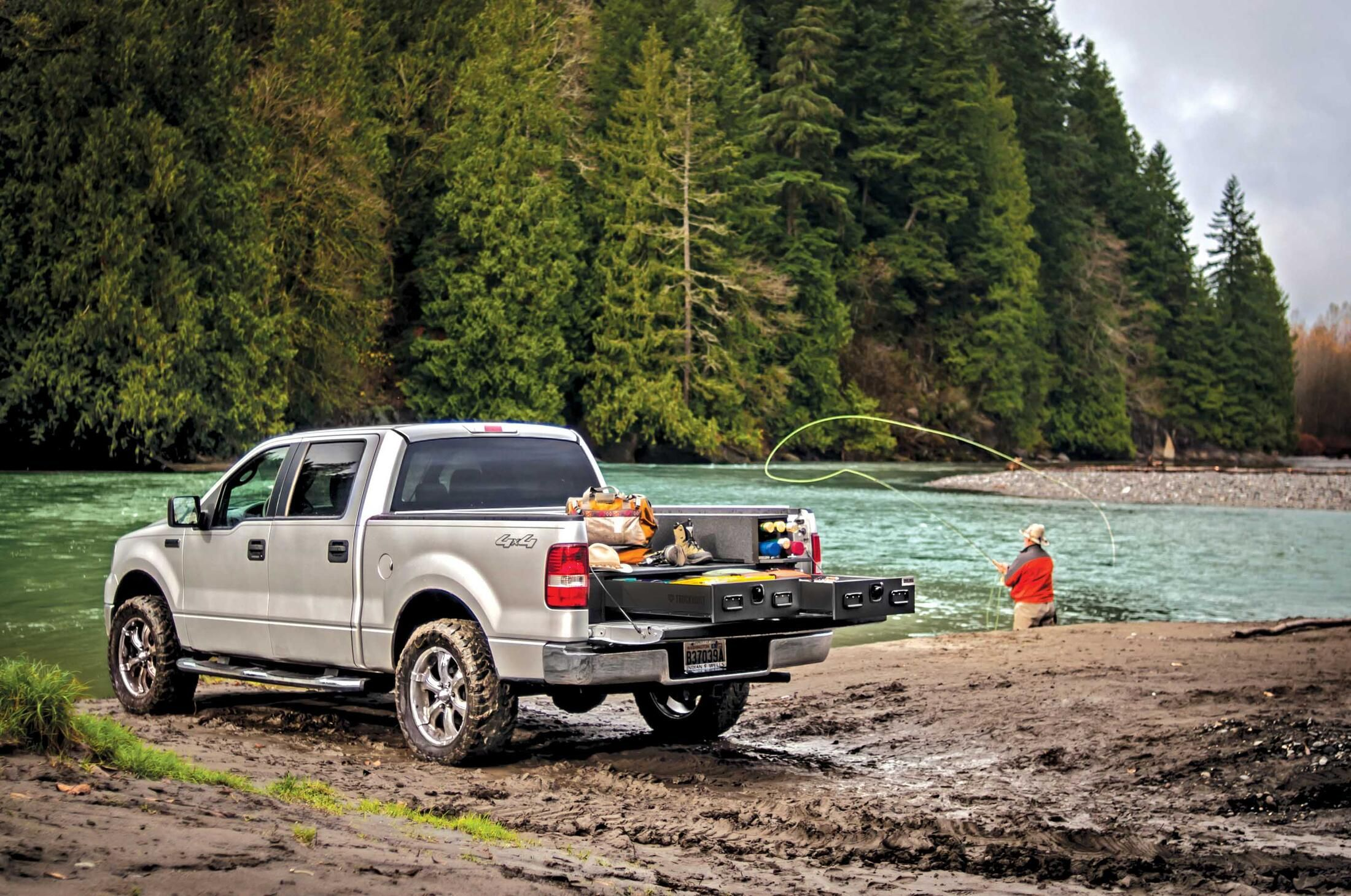 A Silver Ford F-150 filled with fishing gear and a man casting a line in the background.