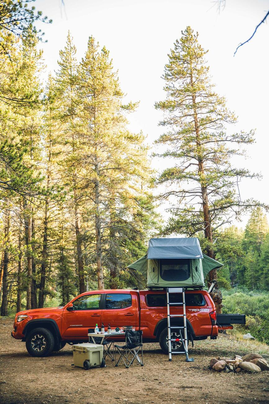 A green tent on top of a red Toyota Tacoma. There is an open TruckVault in the bed of the bed.