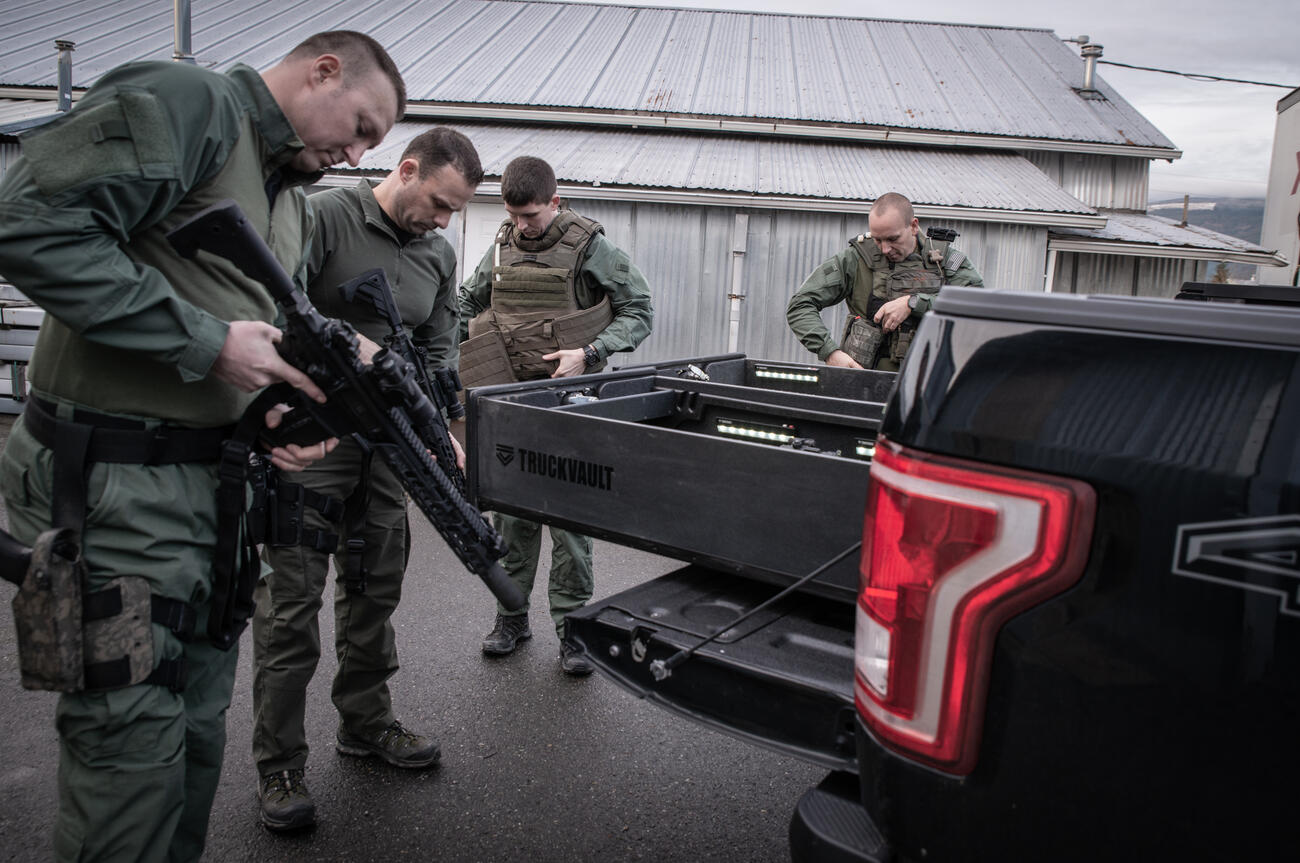 A SWAT team of four checking out their weapons while standing around an all weather TruckVault for a Ford F-150.