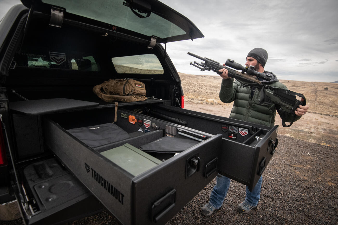 A man placing his rifle into his TruckVault which is in the back of his Ford F-150.