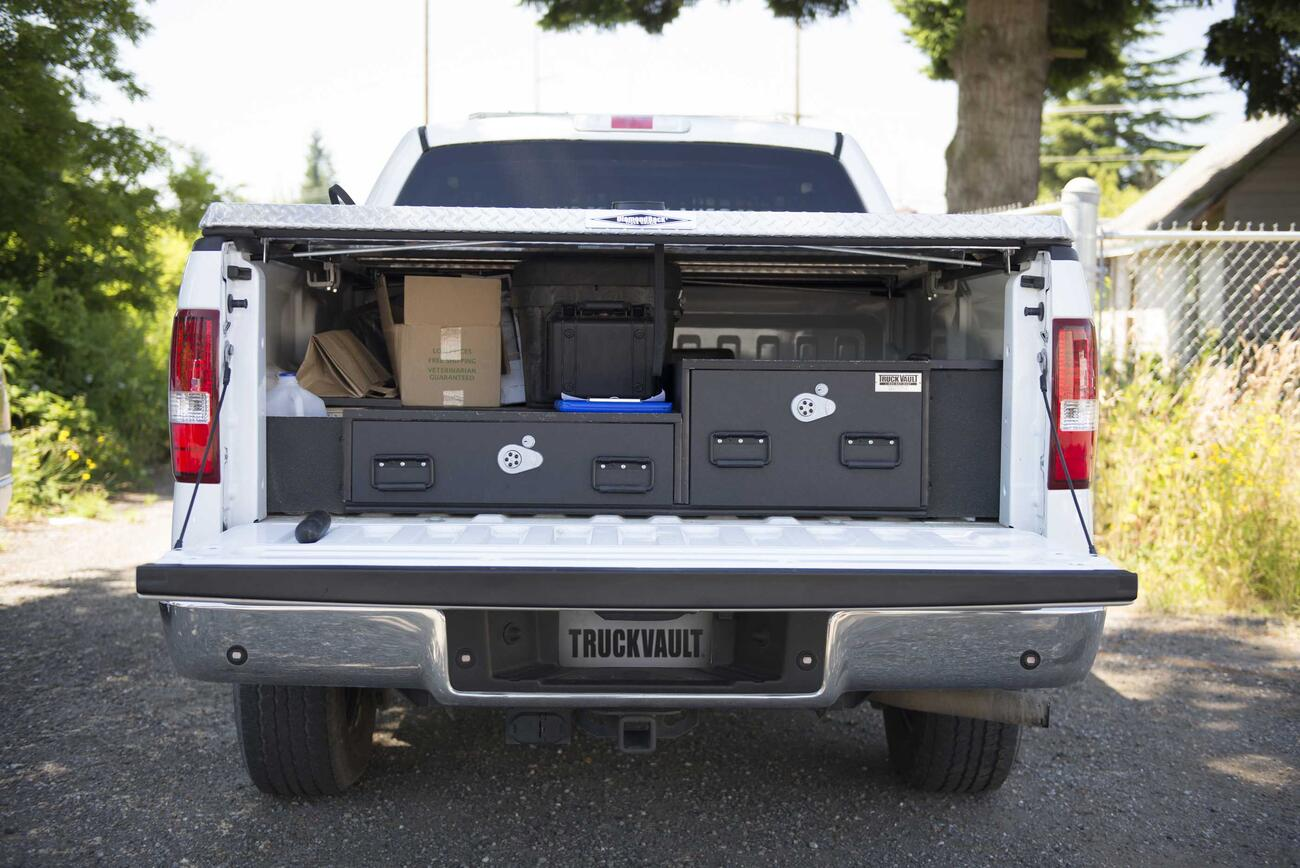 A White Ford F-150 with a covered bed and offset TruckVault drawers.