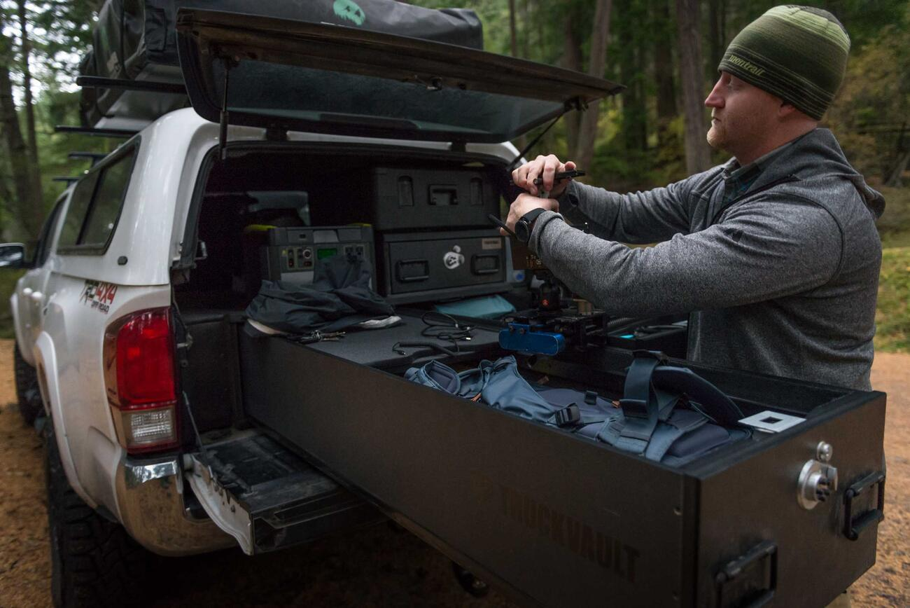 Andy Best taking his camera gear out of a TruckVault in the back of his Toyota Tacoma.
