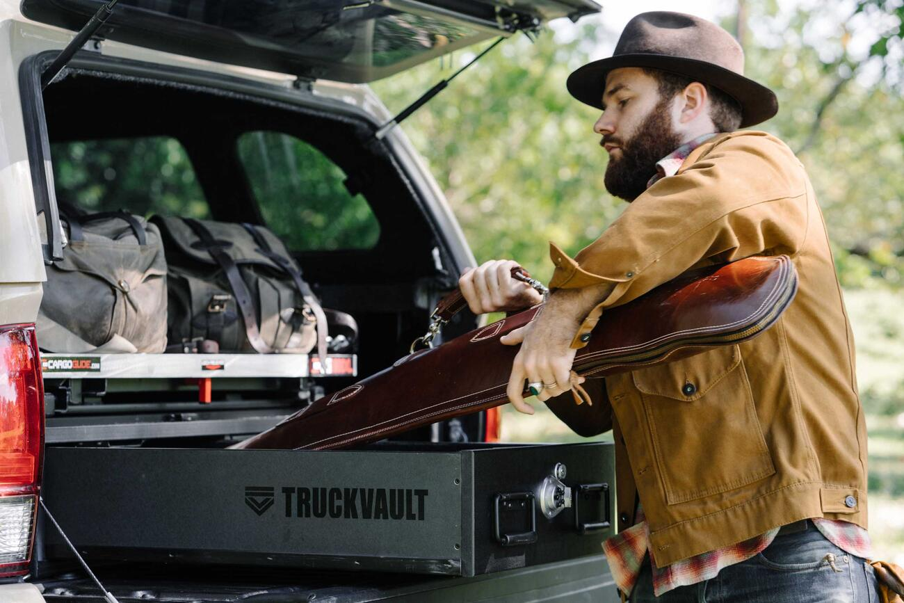 A man placing his shotgun into his TruckVault