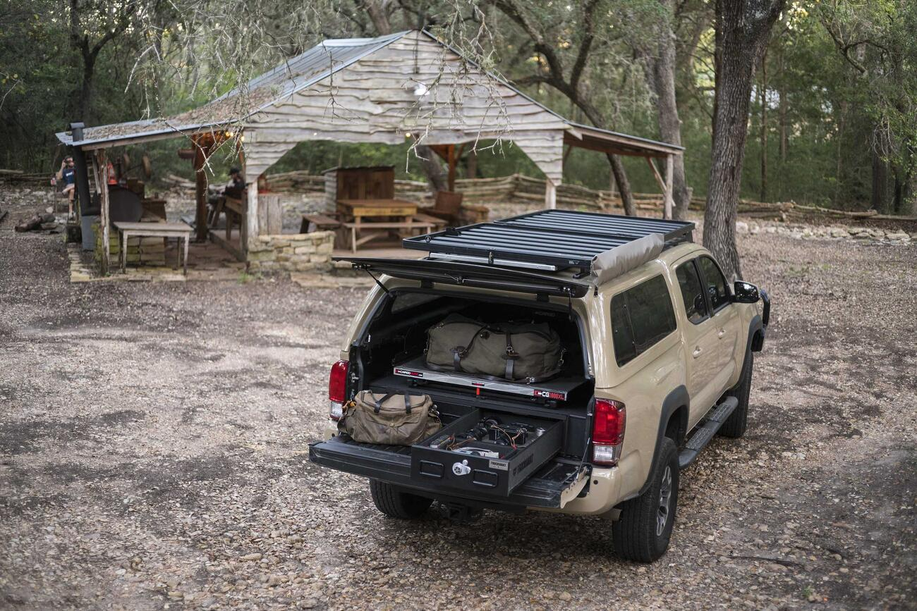 A Toyota Tacoma parked infront of a hut in the woods. Inside of the bed of the Tacoma is an open TruckVault filled with gear.