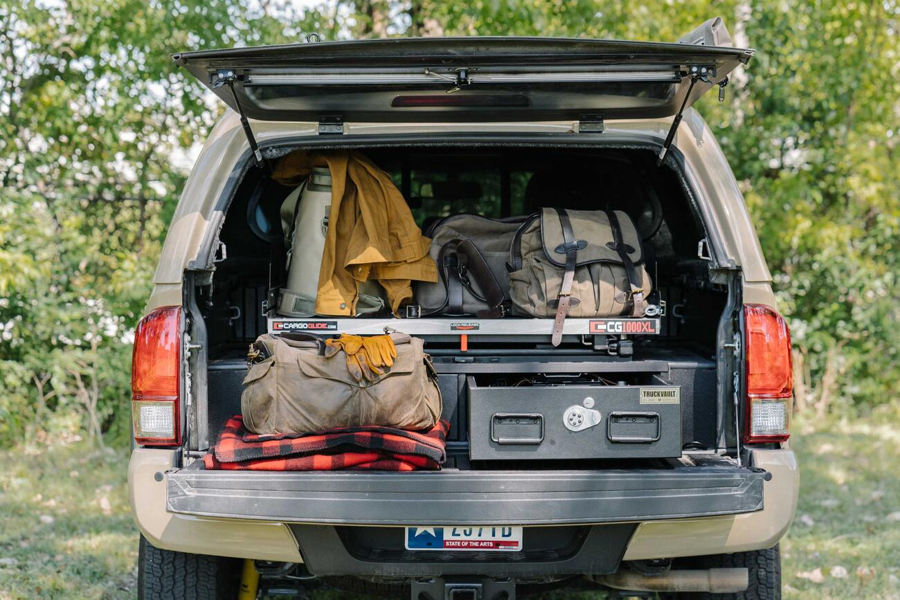 A truck with a canopy and a TruckVualt and a Cargo Glide in the the back. The truck bed area is full of gear, in and on the TruckVault.