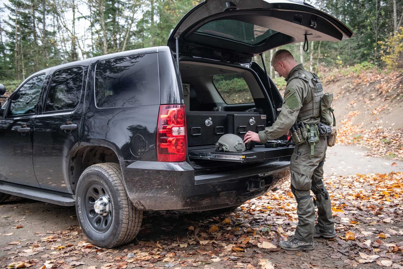 A man in tactical clothing working on a gun that is on top of a heavy duty pull out table in the back of a black Chevy Tahoe.