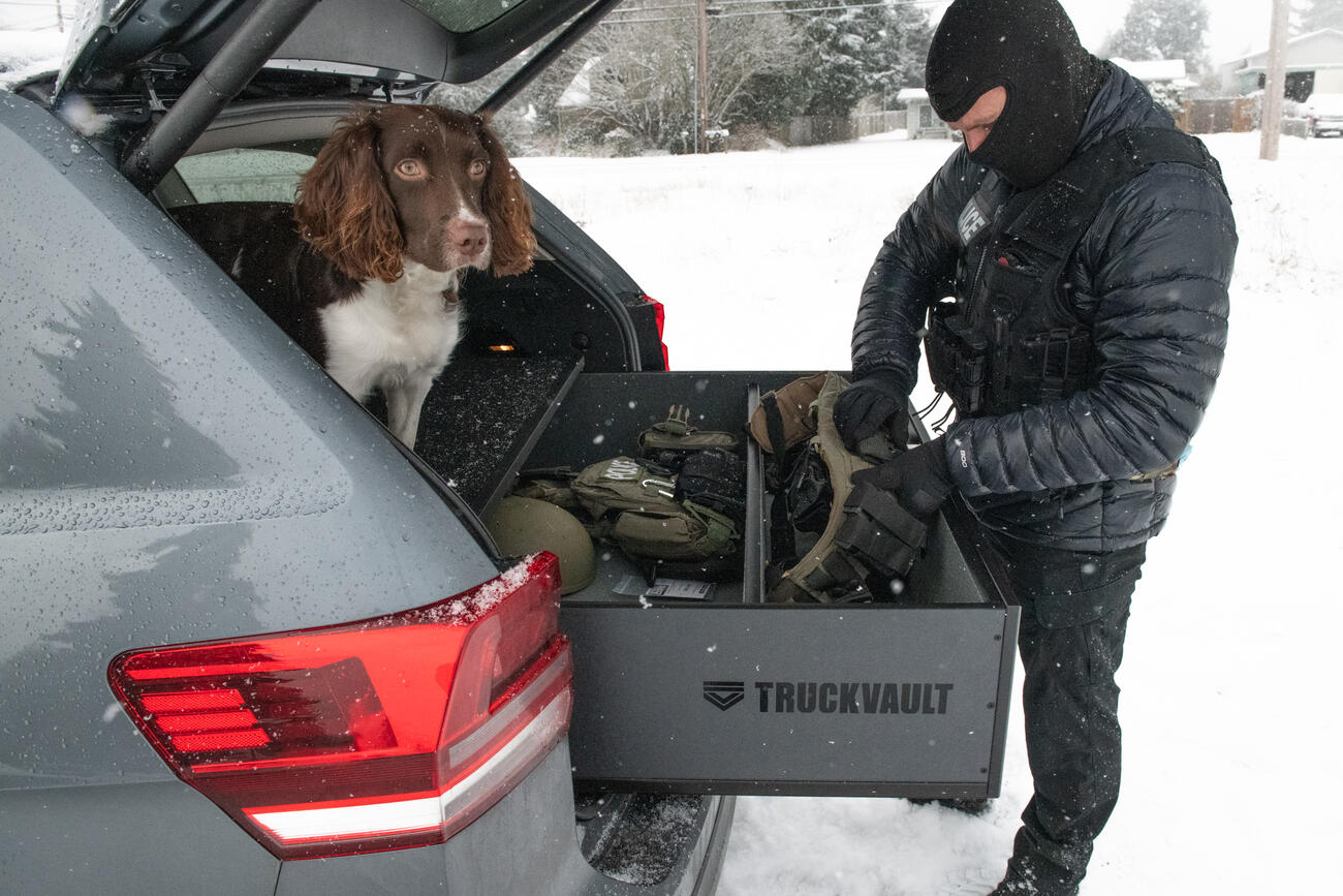A police officer grabbing gear out of a TruckVault, with a dog sitting on top of the TruckVault.