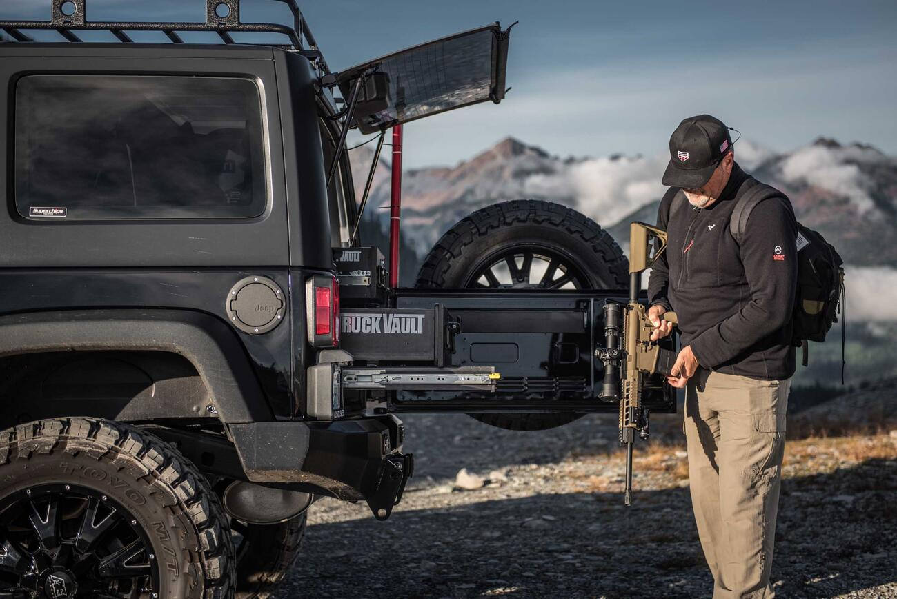 A man holding an assault rifle behind a black Jeep Wrangler with custom TruckVault in the mountains.