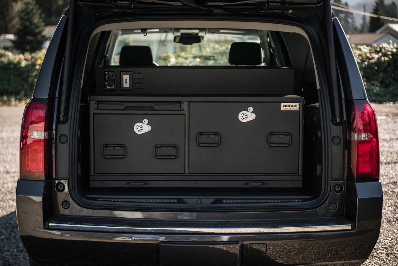 The back of Chevy Suburban with a TruckVault complete with a technology pack and pull-out table.