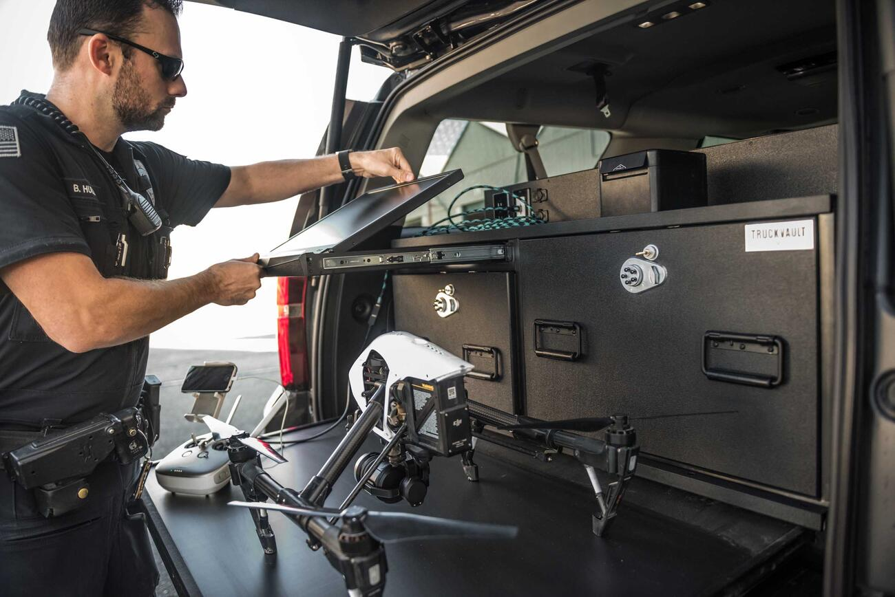 A police officer opening his drone viewing screen on his TruckVault.