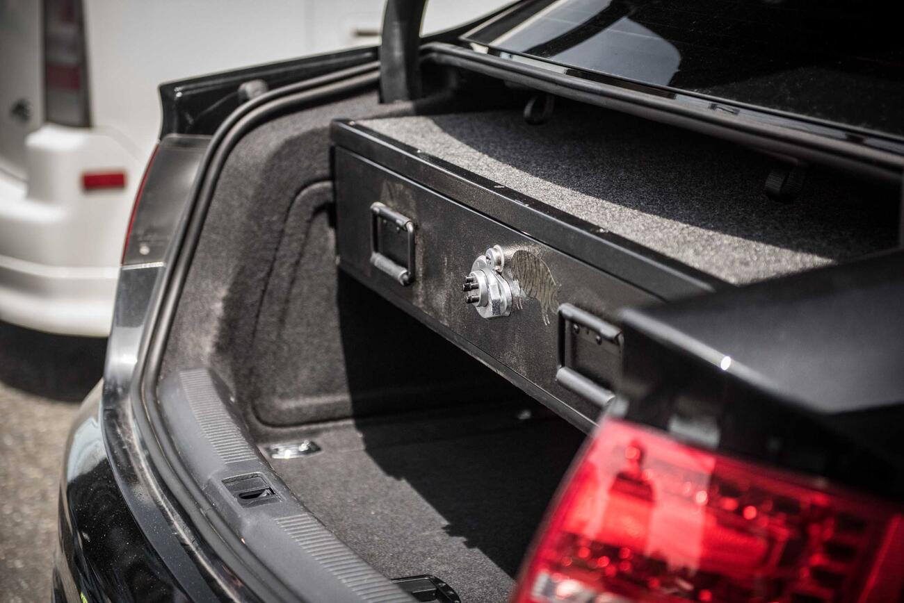 A black Audi sedan with a TruckVault in the cargo area.