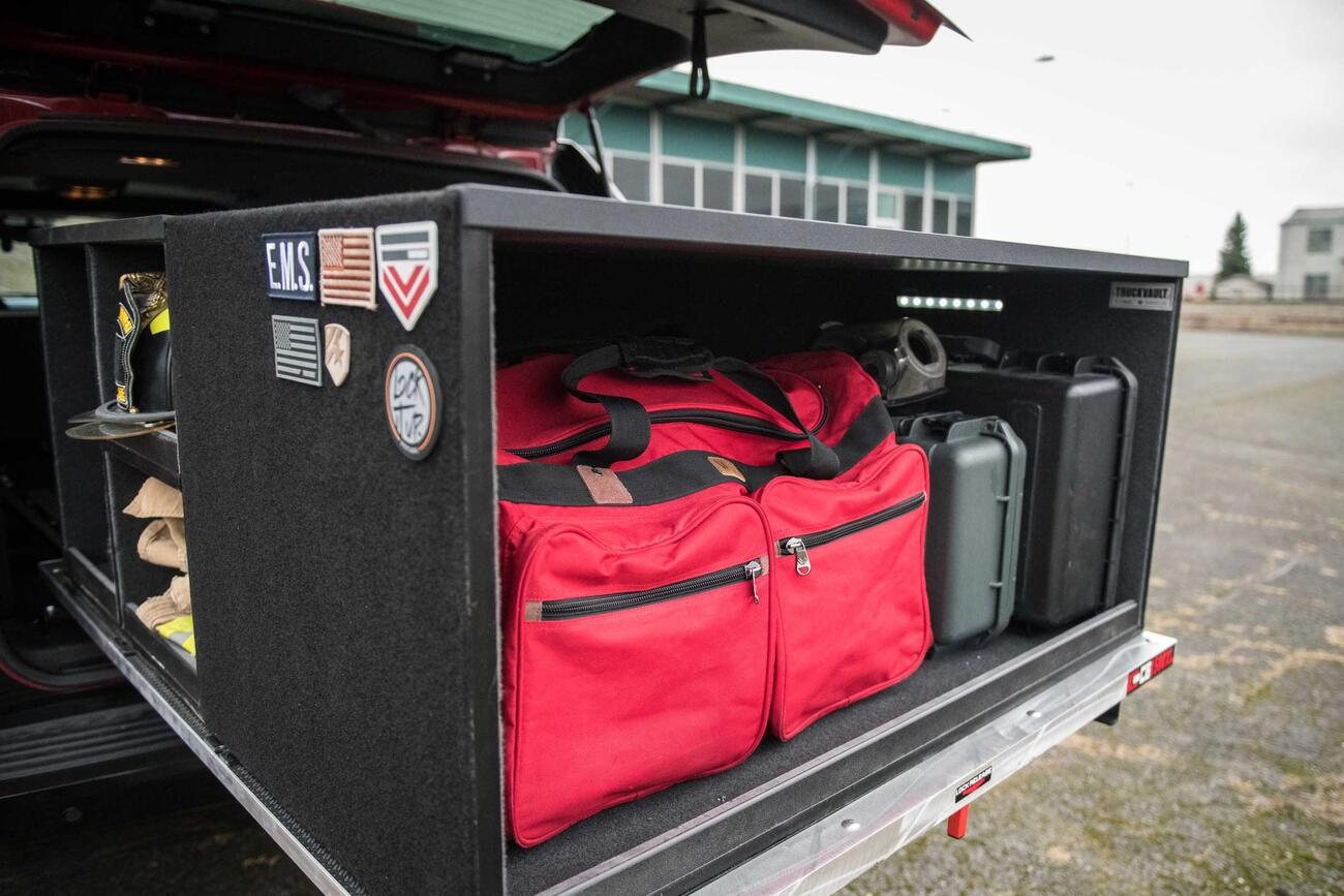 A custom Truckvault in the back of a red Chevy Suburban filled with fire fighting gear.