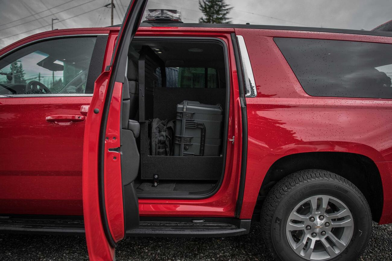 A view inside the read door of a red, fire department Chevy Suburban with a Custom TruckVault inside.