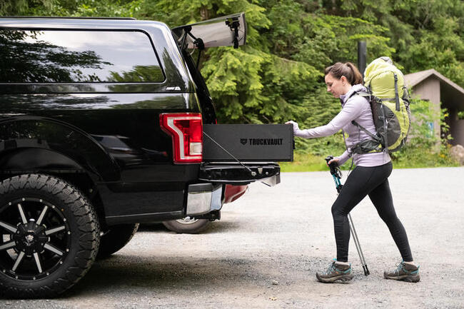 A woman closing her TruckVault storage system while heading out for a hike.
