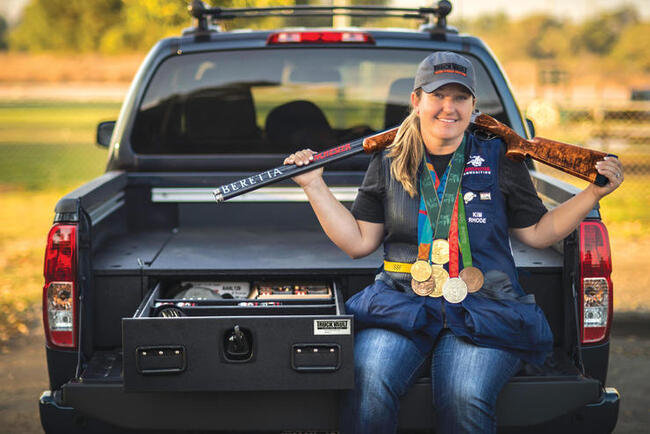 Kim Rhode sitting on the tailgate of her Nissan Titan while holding her Olympic gold medals and competition rifle.