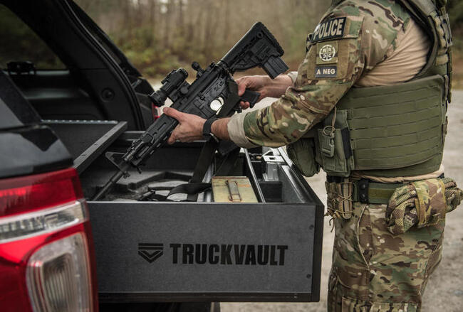 A law enforcement professional taking a firearm out of his TruckVault storage system.