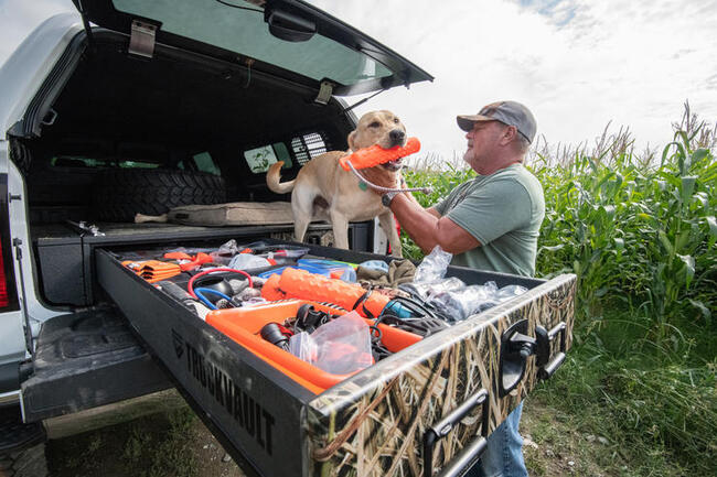 A man with his dog getting his training gear ready in a TruckVault.