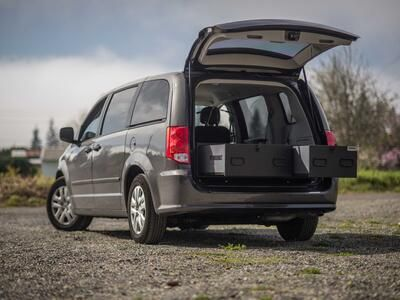 A black Grand Caravan with the trunk open and a magnum height TruckVault inside.