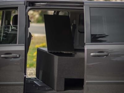 The side of a black Dodge Grand Caravan with a TruckVault inside.