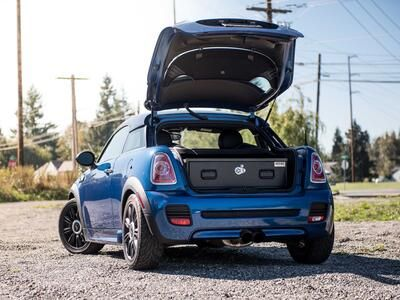 A blue Mini Cooper with an elevated TruckVault in the cargo space.