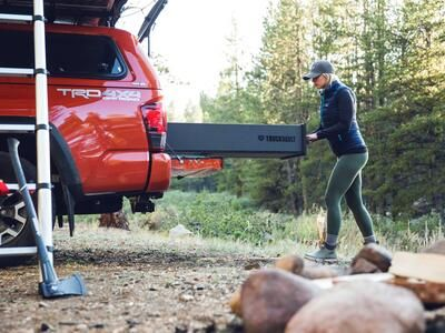 A red truck with a roof tent and a TruckVault. The TruckVault is being opened by a woman.