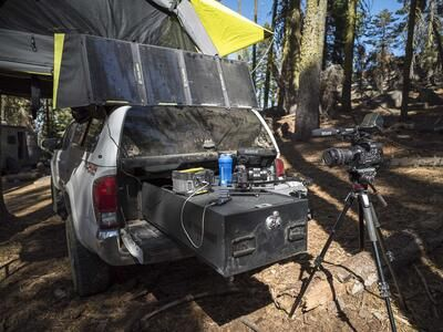 A white Toyota Tundra parked in the woods with a TruckVault filled with camera equipment.