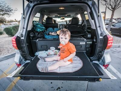 A baby sitting on a heavy duty pull out table in a Lexus LX570.