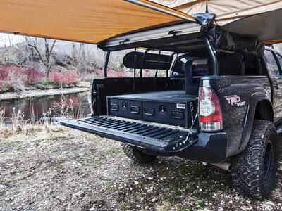 A Toyota Tundra with a TruckVault secure storage system in the bed and a rooftop tent