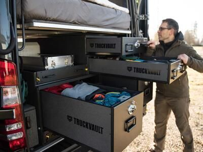 A man rummaging through his TruckVault secure storage system in the back of a Mercedes Sprinter
