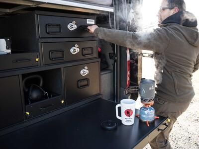 A man opening a TruckVault secure storage system while he brews coffee on a TruckVault extension table.