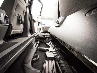 An open SeatVault in the back of a Ford F150 with guns and other police gear.