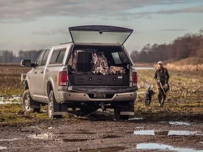 A Ford F-150 with with a Magnum 2 Drawer All-Weather TruckVault storage system in it, sitting in a muddy field.