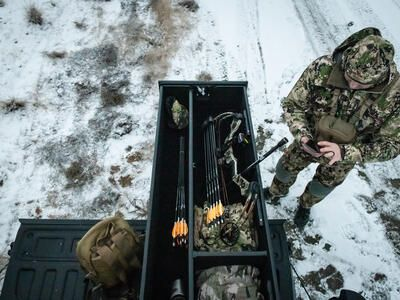 A man in camouflage checking his phone next to a TruckVault with a compound bow inside of it.