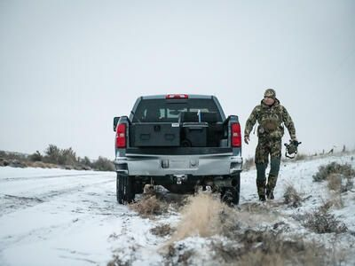 A man in camouflage with a bow walking away from a parked Chevy Silverado with a Half Width TruckVault in the bed.