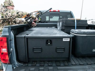 A man in camouflage placing his bow on top of a Half Width TruckVault.