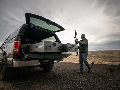 A man grabbing his assault rifle out of the back of his TruckVault in a Ford F-150.