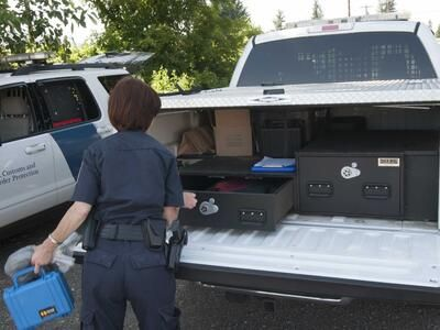 A U.S. Customs and Border Protection officer taking gear out of her White Ford F-150.