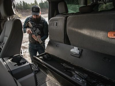 A man checking his rifle before he places it into a SeatVault.