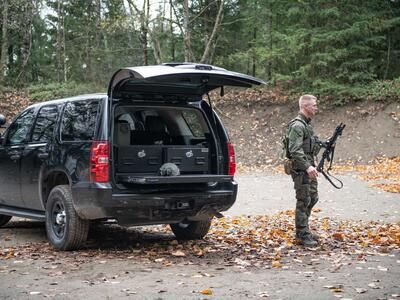 A man in tactical clothing holding a gun walking behind a black Chevy Tahoe complete with a TruckVault and a heavy duty pull out table.