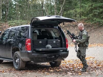 A man in tactical clothing holding a gun walking behind a black Chevy Tahoe complete with a TruckVault and heavy duty pull out table.