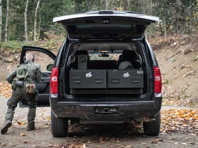 A man in tactical clothing taking cover behind a black Chevy Tahoe with a TruckVault inside of it.